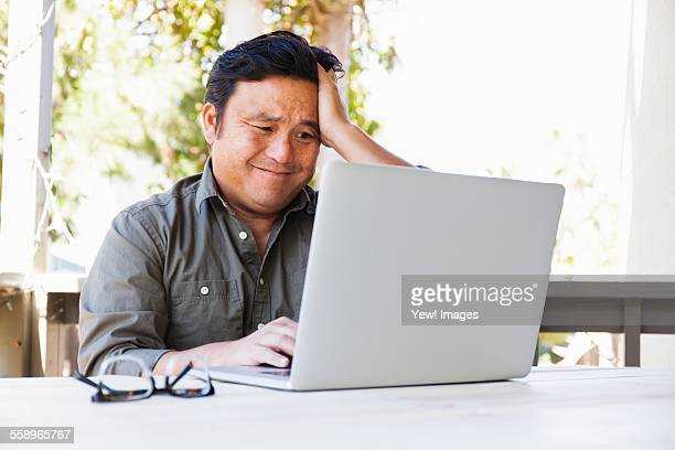 Frustrated mature businessman working on laptop in porch