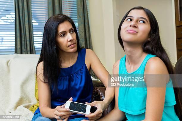 Frustré mère tenant cassé le téléphone intelligent tout en parlant preteen