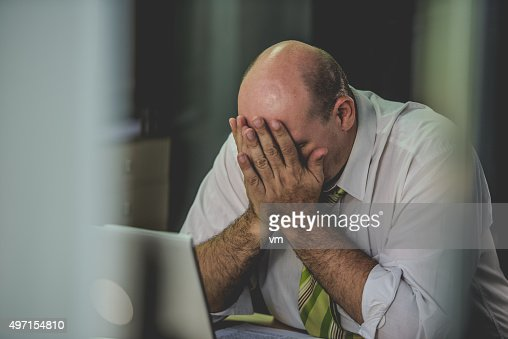 Frustrated office worker with his head in his hands