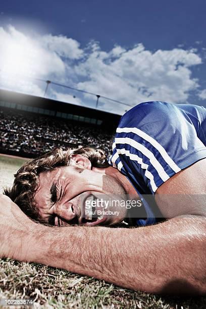 Frustriert Fußballspieler Leg dich mit dem Rücken auf dem Boden