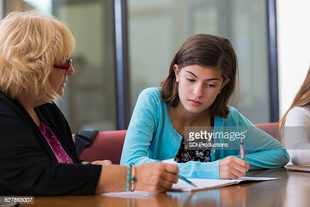 Frustrated student working with tutor on math assignment after school