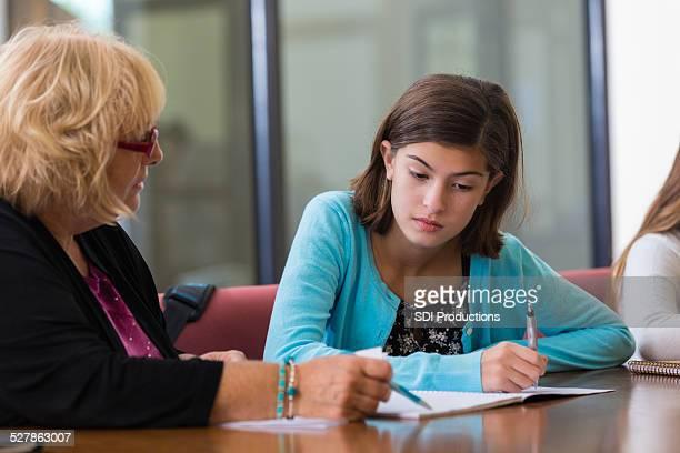 Frustrierter Schüler arbeiten mit tutor auf Mathematik assignment nach der Schule