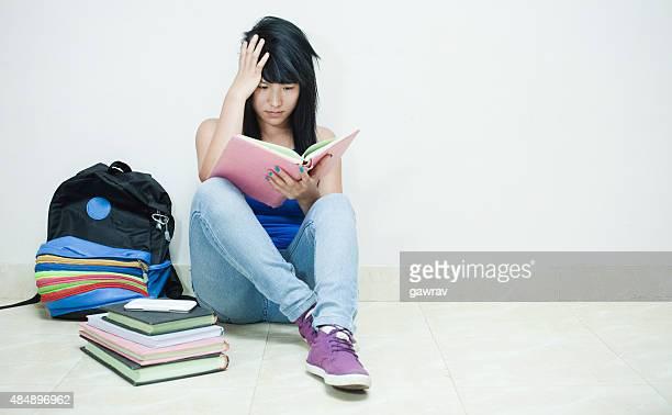 Verärgert junge asiatische Mädchen-student auf Etage Sie ein Buch lesen.