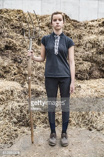 Frustrated teenage girl with pitchfork in front animal dung hill