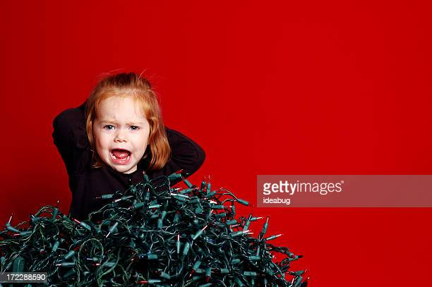 Frustrated Toddler with Pile of Tangled Christmas Lights