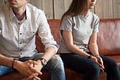 Frustrated unhappy young couple sitting on sofa after fight, disappointed boyfriend and offended girlfriend breaking up thinking of problems in bad relationships, misunderstandings and insult concept
