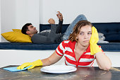 Frustrated woman cleaning room with lazy man relaxing on couch at home
