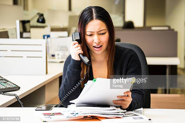 Frustrated woman in an office on the phone