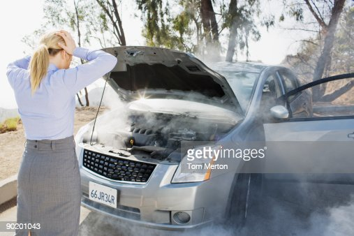 Frustrated woman looking at smoking car engine : Stock Photo