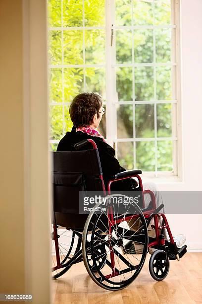 Frustration! Frau im Rollstuhl zu beobachten, die von den Garten