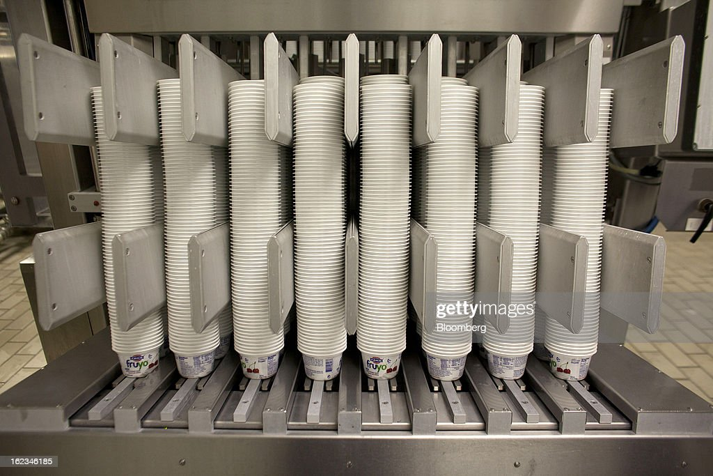 Fruyo-branded yoghurt cartons stand in a machine before processing at the Fage Dairy Industry SA plant in Athens, Greece, on Thursday, Feb. 21, 2013. An October restructuring that placed Fage International SA's Greek units in a subsidiary called Fage Dairy Industry SA coincided with Coca-Cola Hellenic Bottling SA's plan to flee the epicenter of Europe's debt crisis by moving its main stock listing to London from Athens. Photographer: Kostas Tsironis/Bloomberg via Getty Images