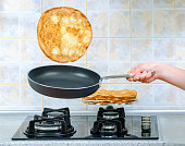 girl's hand holding a frying pan and turns the yeast pancake
