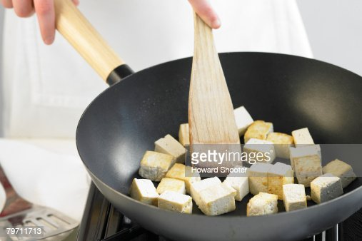 Frying tofu in a wok, close up