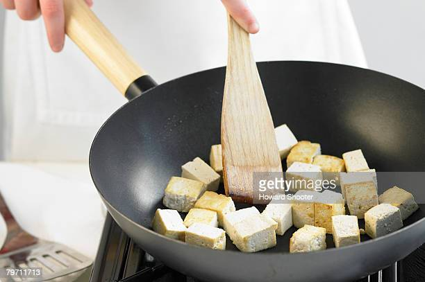 Frying tofu in a wok, close up