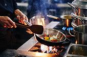 Hands of cook frying vegetables on pan