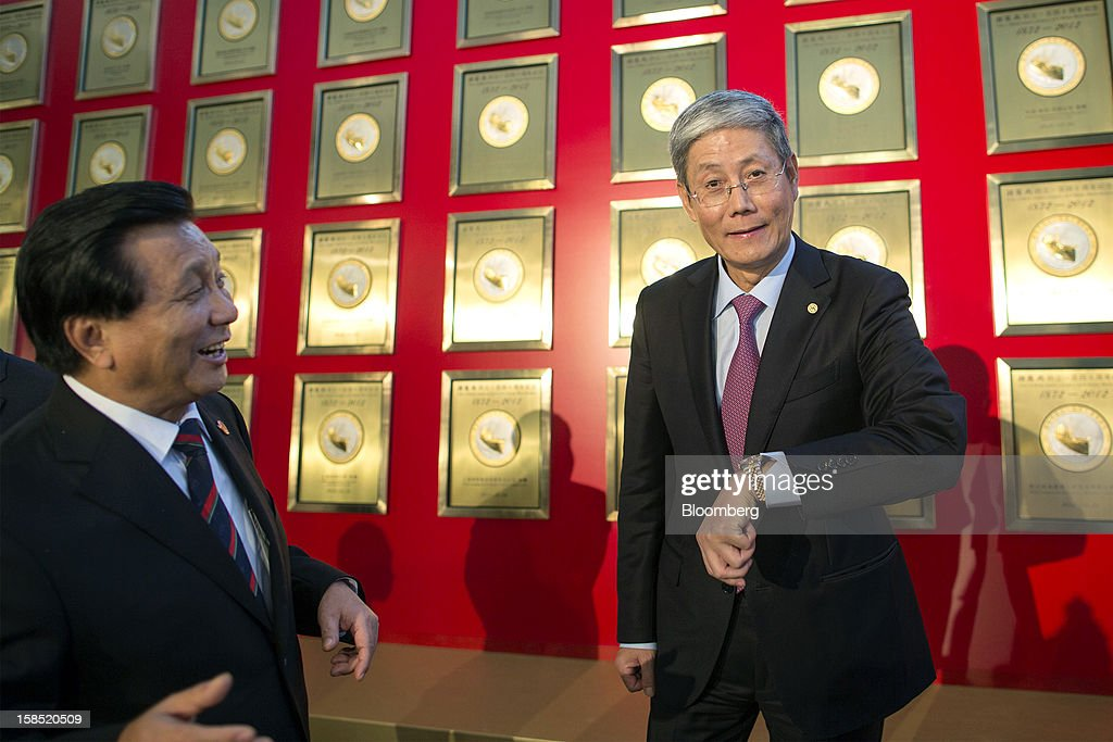 Fu Yuning, chairman of China Merchants Group Ltd., right, checks the time as Hu Zheng, vice president of China Merchants Group Ltd., looks on as they stand alongside a selection of commemorative plaques celebrating the company's 140th anniversary prior to a news conference in Hong Kong, China, on Tuesday, Dec. 18, 2012. China Merchants Group, an investment holding company, comprises of property management, transportation and financial investment businesses. Photographer: Jerome Favre/Bloomberg via Getty Images