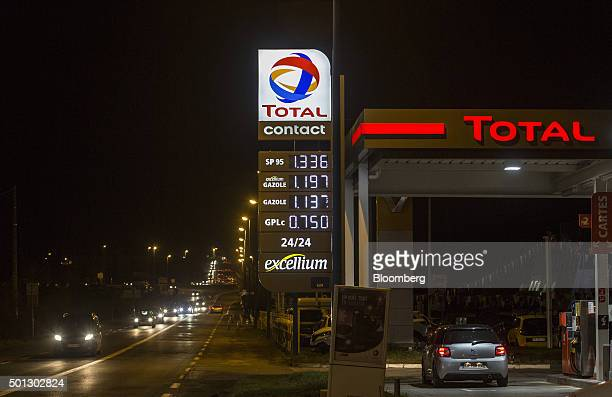 Fuel prices sit illuminated on a sign as an automobile stands beside petrol pumps on the forecourt of a gas station operated by Total SA at night in...