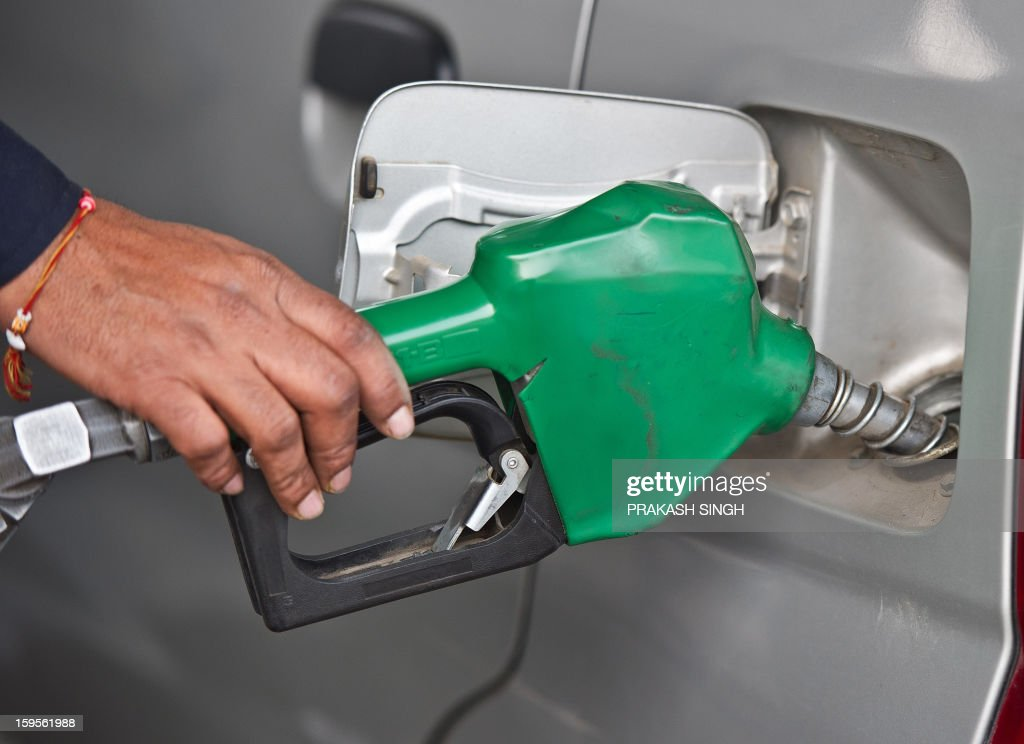 A fuel pump employee fills petrol in a car in New Delhi on January 16, 2013. Petrol price was hiked late January 15 night by about 35 paise per litre in line with firming raw material cost. Petrol will cost Rs 67.56 per litre in Delhi with effect from midnight, as the state government withdrew VAT exemption on the fuel. AFP PHOTO/ Prakash SINGH