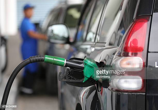 A fuel pump handle rests in the refilling nozzle of an automobile a gas station operated by KazMunayGas National Co in Almaty Kazakhstan on Wednesday...