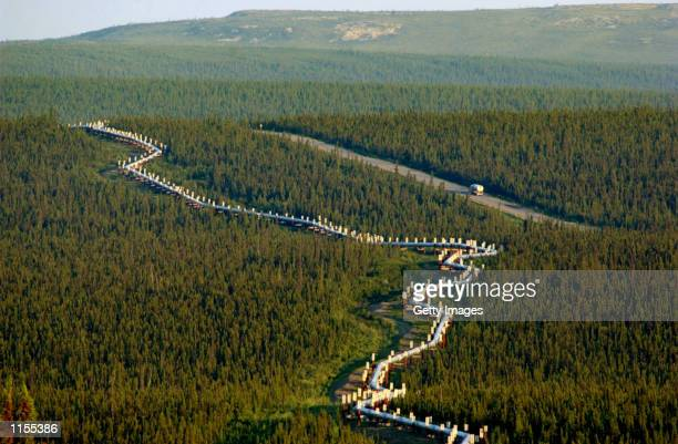 A fuel truck drives south along the TransAlaska Pipeline late on July 21 2002 between the Yukon River and The Arctic Circle on Dalton Hwy The 800...