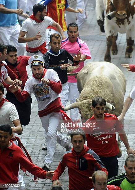 A Fuente Ymbro bull hooks a participant's sash during the sixth bull run of the San Fermin Festival in Pamplona northern Spain on July 12 2014 The...