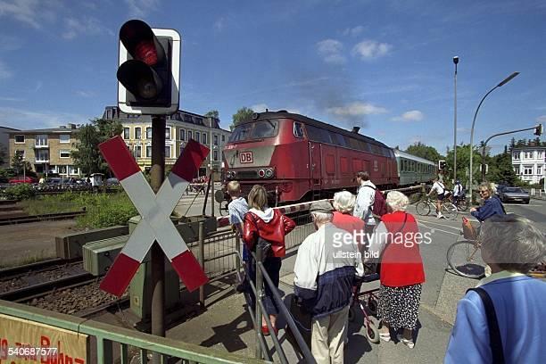 Fußgänger warten hinter einem beschrankten Bahnübergang den ein Zug passiert Im Vordergrund eine Ampel mit Andreaskreuz Bahnschranke Schranke