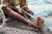 Fujairah, UAE, A local fisherman fixes holes and tangles in his net in Fujairah.