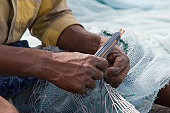 Fujairah, UAE, A local fisherman fixes holes and tangles in his net in Fujairah.