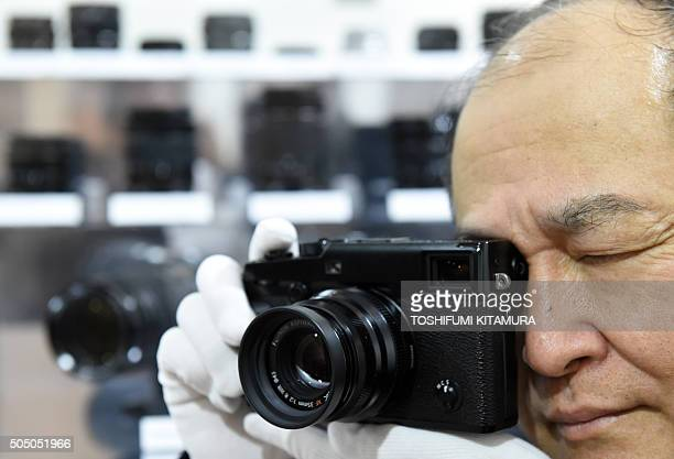 A Fujifilm employee poses with the company's new XPro2 premium mirrorless digital camera during the Fujifilm X Series fifth anniversary event in...
