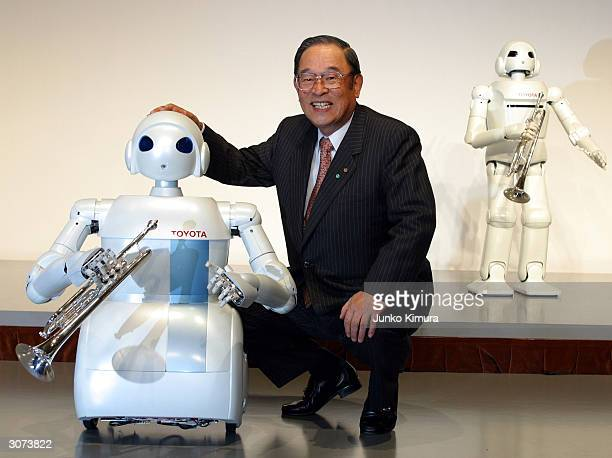 Fujio Cho the President of Toyota Motor Corporation poses next to the companies newly developed prototype of a rolling robot during a press...