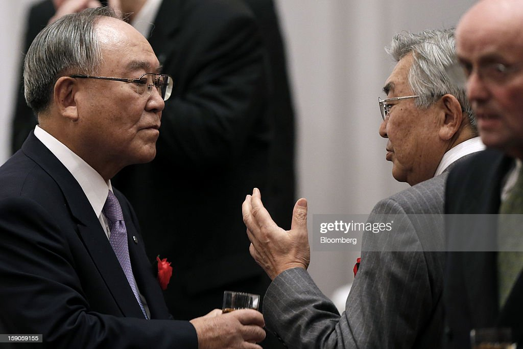 Fujio Mitarai, chairman and chief executive officer of Canon Inc., left, speaks with Atsushi Saito, chief executive officer of Japan Exchange Group Inc., second right, at a New Year's party for business leaders in Tokyo, Japan, on Monday, Jan. 7, 2013. The Japanese government will announce around 12 trillion yen ($136 billion) in fiscal stimulus measures to boost the nation's shrinking economy, Japanese media reported today. Photographer: Kiyoshi Ota/Bloomberg via Getty Images