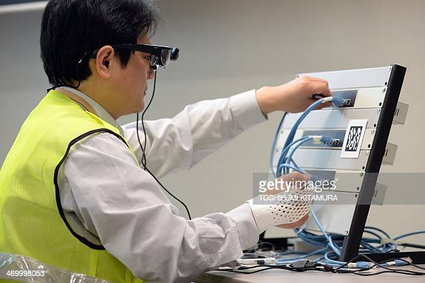 A Fujitsu employee demonstrates the company's new technology glovestyle wearable device which can read NFC tag to display the information onto a head...