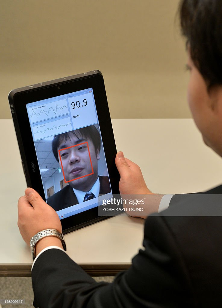 A Fujitsu engineer demonstrates new technology, a the real-time pulse monitor system with facial imaging technology, that ustilises a web-camera in PCs or smartphones, at the company's headquarters in Tokyo on March 18, 2013. Fujitsu develped the technology to measure the user's pulse via the brightness of their face. AFP PHOTO / Yoshikazu TSUNO