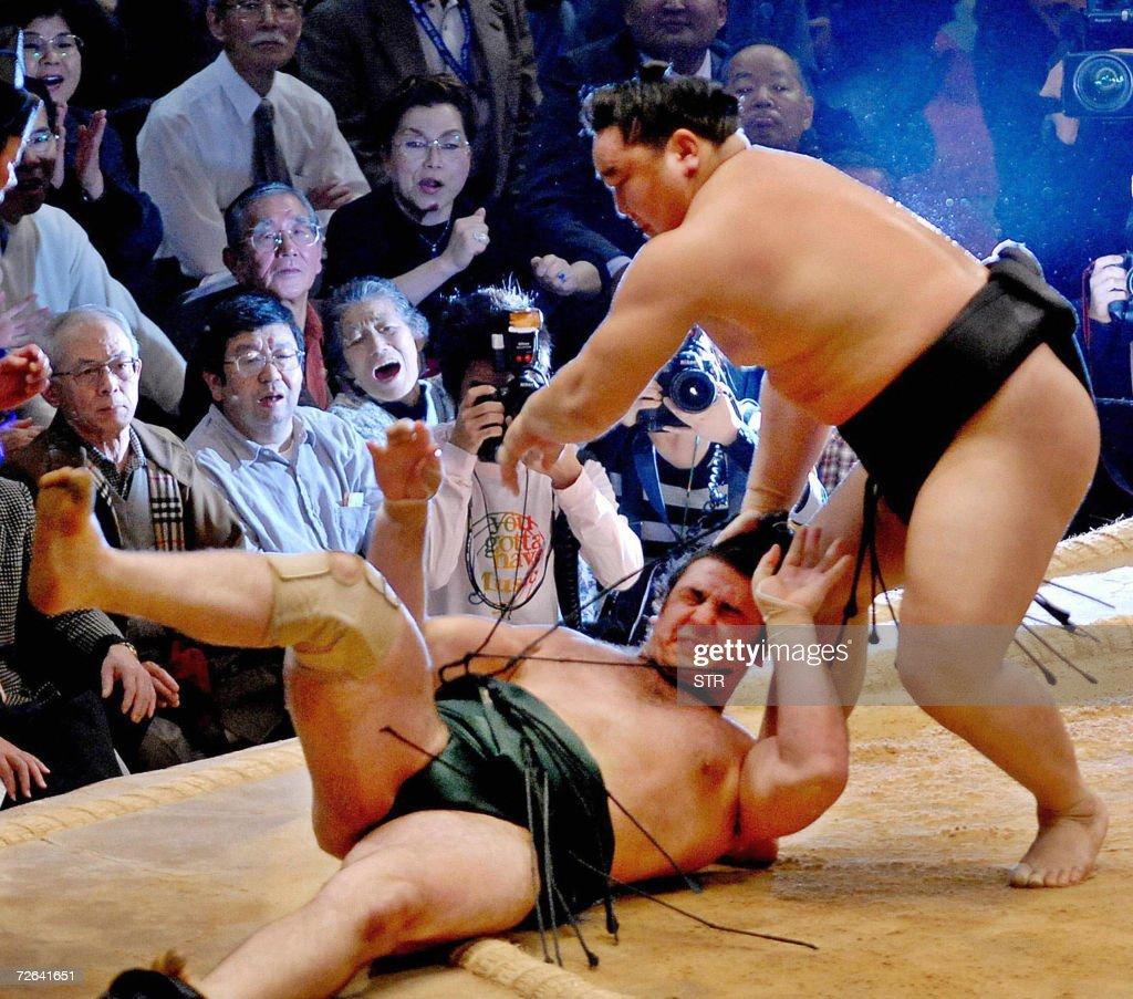 Mongolian sumo grand champion Asashoryu throws Bulgarian champion Kotooshu to the ground to win his 19th Emperor's Cup at the Kyushu Grand Sumo...
