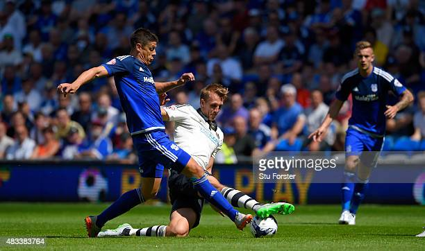 Fulham defender Dan Burn is challenged by Cardiff striker Alex Revell during the Sky Bet Championship match between Cardiff City and Fulham at...