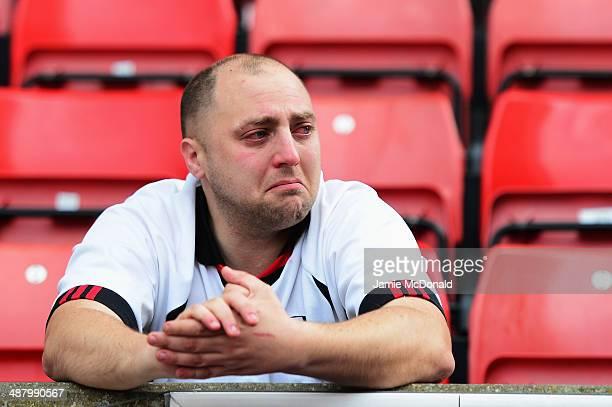 Fulham fan reacts as his side are relegated following their defeat in the Barclays Premier League match between Stoke City and Fulham at the...