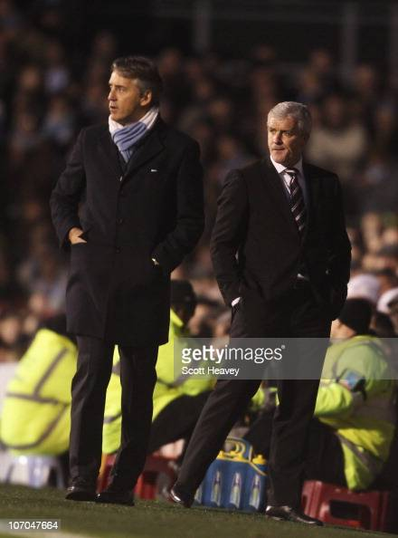 Fulham manager Mark Hughes looks on with Manchester City manager Roberto Mancini during the Barclays Premier League match between Fulham and...