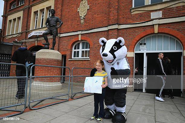 Fulham mascot Billy the Badger poses with a fan outside the ground prior to the Barclays Premier League match between Fulham and Crystal Palace at...