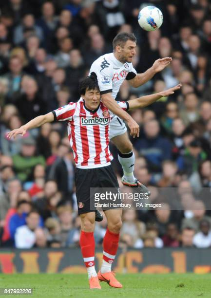 Fulham's Aaron Hughes and Sunderland's Dong Won Ji jump for the ball during the Barclays Premier League match at Craven Cottage London