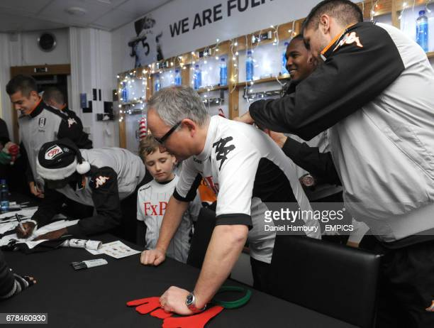 Fulham's Aaron Hughes signs an autograph during Christmas at the Cottage
