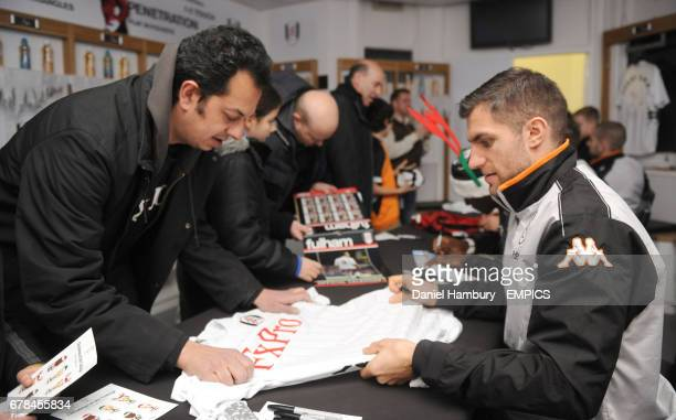 Fulham's Aaron Hughes signs autographs and pose for pictures during Christmas at the Cottage