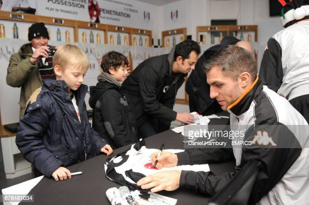 Fulham's Aaron Hughes signs autographs and poses for pictures during Christmas at the Cottage