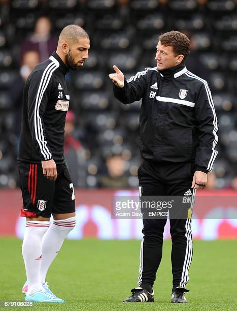 Fulham's Ashkan Dejagah speaks with first team coach Billy McKinlay during warmup
