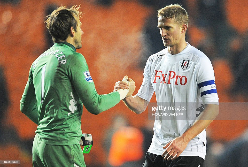"""Fulham's Australian goalkeeper Mark Schwarzer (L) congratulates matchwinner Norwegian defender Brede Hangeland (R) during the English FA Cup third round replay football match between Blackpool and Fulham at Bloomfield Road in Blackpool, northwest England, on January 15, 2013. USE. No use with unauthorized audio, video, data, fixture lists, club/league logos or """"live"""" services. Online in-match use limited to 45 images, no video emulation. No use in betting, games or single club/league/player publications."""