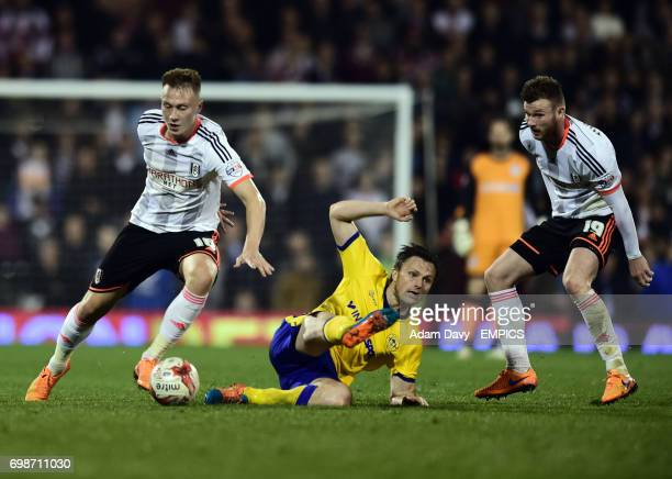 Fulham's Cauley Woodrow and Ryan Tunnicliffe battle with Wigan Athletic's William Kvist
