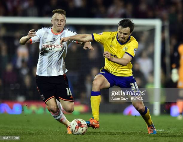 Fulham's Cauley Woodrow and Wigan Athletic's William Kvist battle for the ball