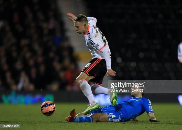 Fulham's Cauley Woodrow battle for the ball with Sunderland's Jordi Gomez