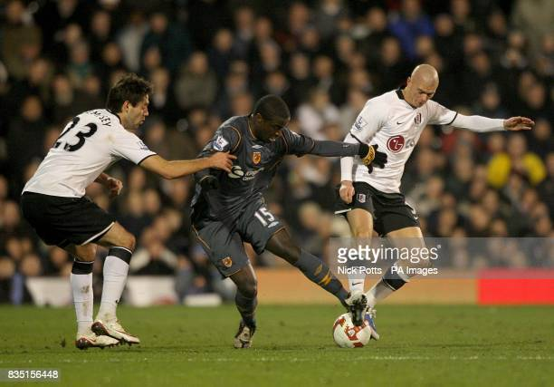 Fulham's Clint Dempsey and Paul Konchesky challenge Hull City's Bernard Mendy for the ball
