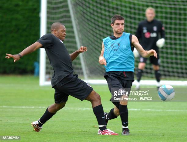 Fulham's Collins John and Aaron Hughes compete during training