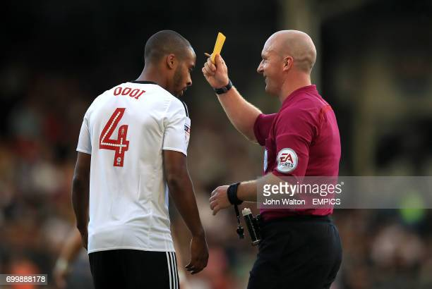 Fulham's Dennis Odoi is shown a yellow card by referee Simon Hooper